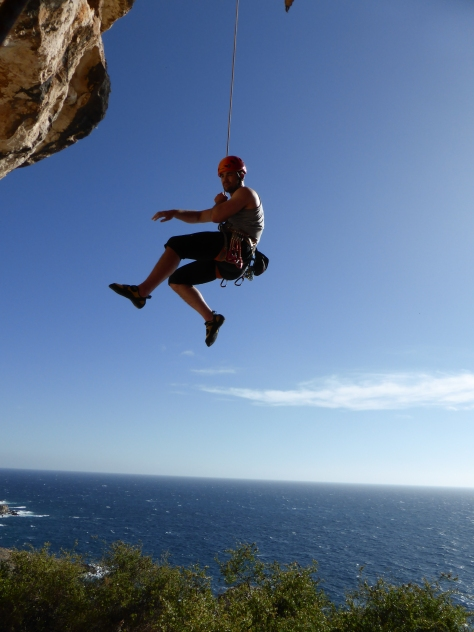 A picture of Jesse dangling in midair from the top of a very overhanging climbing route. The background shows the sea and a clear blue sky.