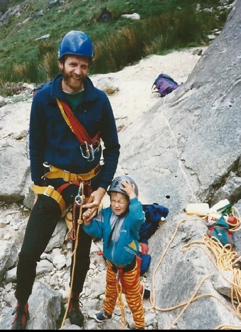 A picture of Jesse aged 2 holding hands with his dad at the bottom of Idwal Slabs. Both are wearing climbing gear and helmets ready to climb.