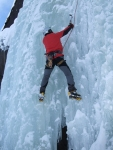 A picture of Jesse ice climbing in Norway. He is using axes and crampons to climb a frozen waterfall. It looks very cold, he is wearing a big red jacket.