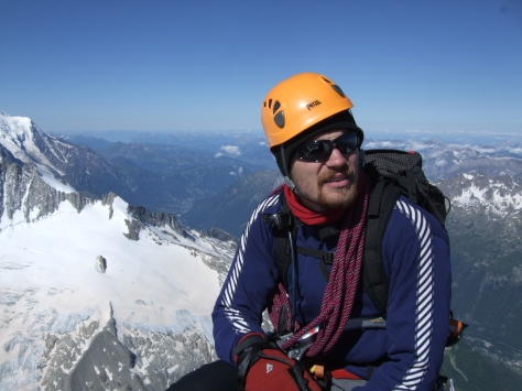 A picture of Jesse sat at the top of a mountain in the alps with snowy peaks in the background. He is wearing an orange helmet, has a rope coiled over his shoulder and is holding an ice axe.