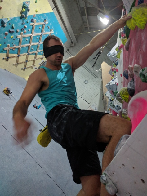 A picture of Jesse hanging off a jug one handed while training at his local indoor wall. His is blindfolded and looks quite tired.