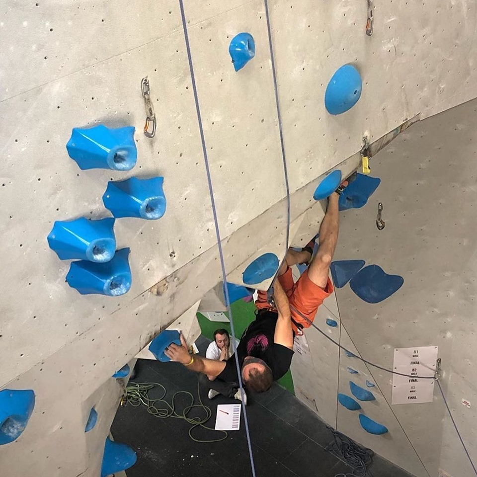 A picture of Jesse competing in an indoor climbing competition. He is climbing a very overhanging roof, making a long reach out to a blue volcano style hold, with his heel resting on a volume.