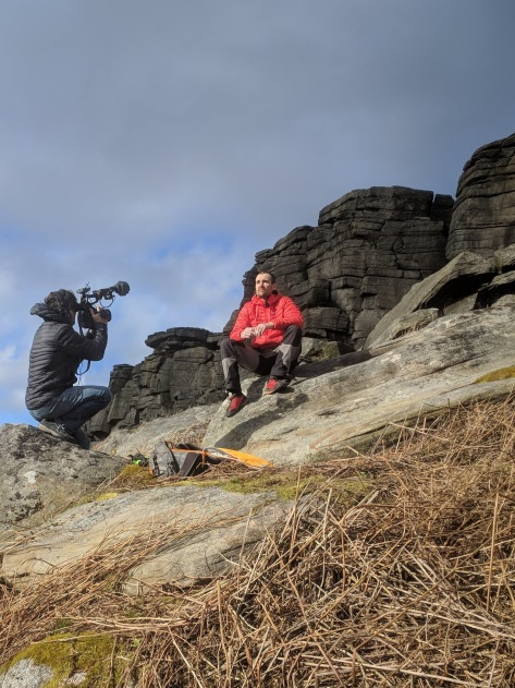 A picture of Jesse sat on a rock wearing his red jacket in the centre of the picture. Alastair is squatting to one side of him with his big camera filming an interview. The gritstone crag of Stanage popular is in the background.