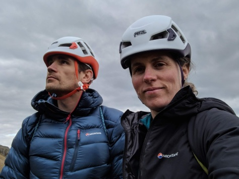 A picture of Jesse and Molly, both wearing Petzl climbing helmets and Montane jackets. Molly is looking at the camera and Jesse is looking out into the distance. They are wearing coiled ropes on their backs as the approach the crag.
