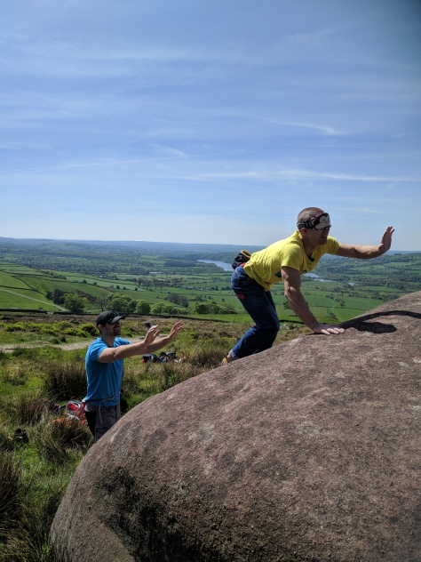 A picture of Jesse and Neil bouldering at the roaches. Jesse is stood at the base of the boulder with both arms in the air, spotting neil. Neil is wearing a monkey eye mask and is reaching out into midair trying to search for the next hold. He is squatting down and reaching forward in an extremely funny pose.