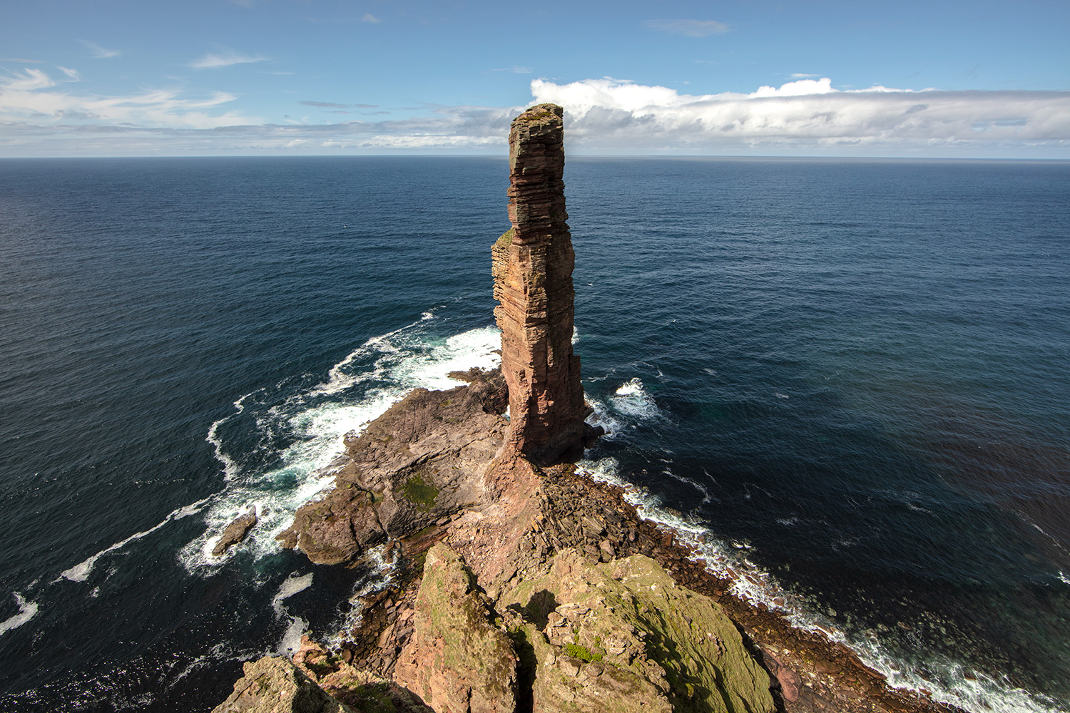 A picture of the Old Man of Hoy taken from the headland looking out to sea. The sea stack is 137 meters tall and is standing proud right in the middle of the picture. Waves are crashing around its base and it is a beautiful blue sky day.