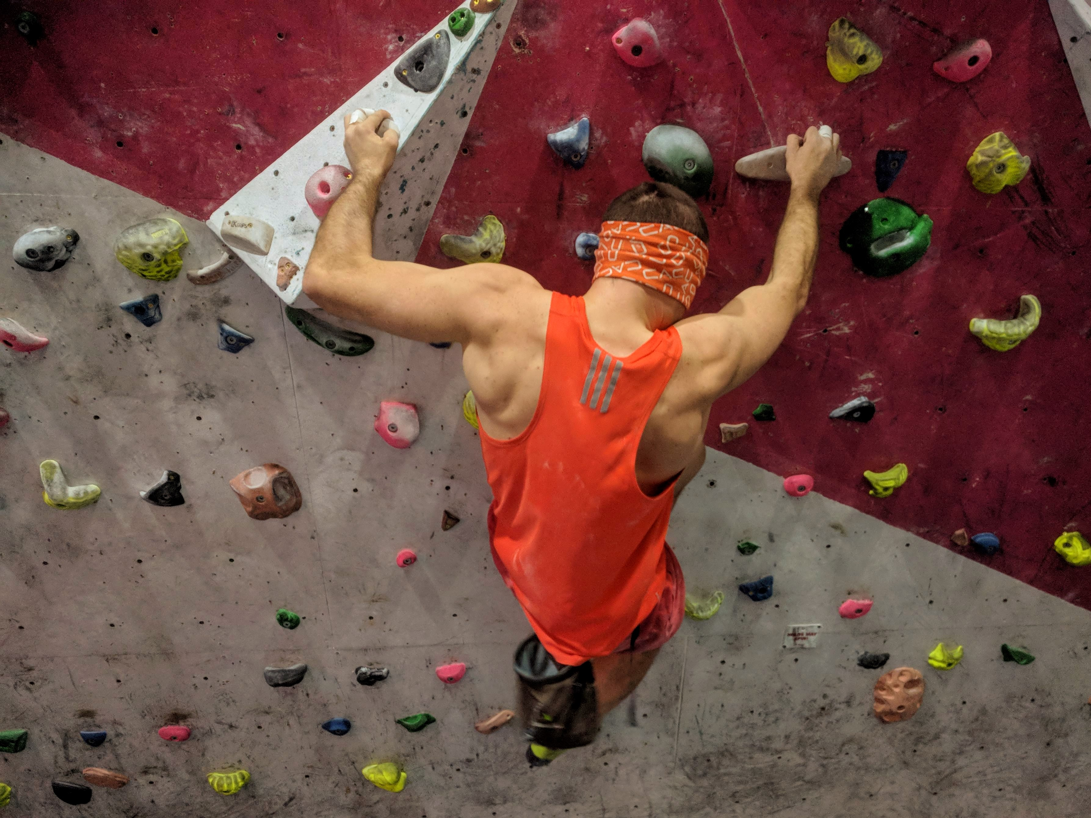 A picture of Jesse wearing an orange vest and an orange blindfold. He is climbing on the wooden holds on the steep circuit board at his local climbing wall.