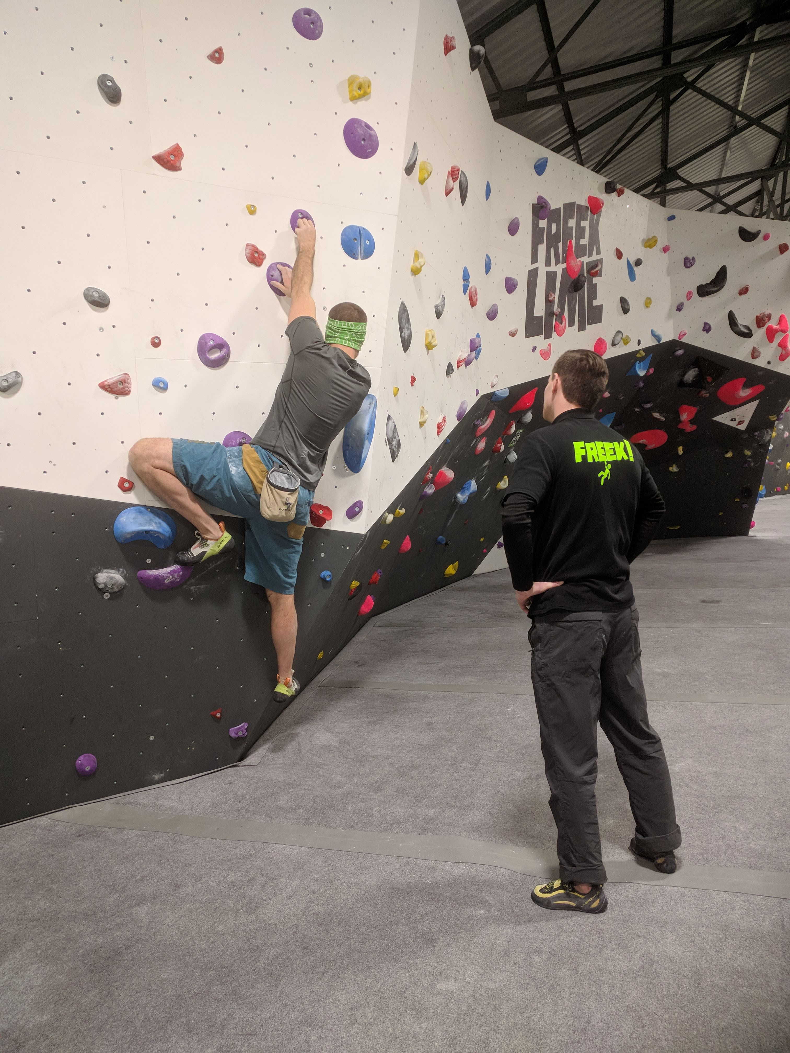 A picture of Jesse climbing a boulder problem with purple pockety holds. A member of staff is stood on the mat behind Jesse acting as his sight-guide.