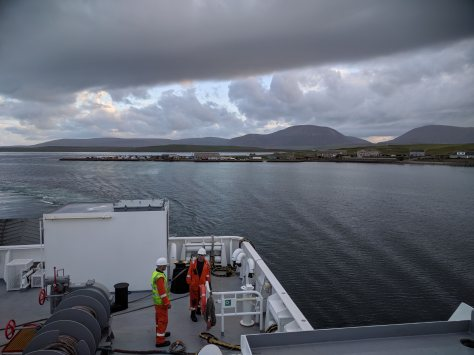 A picture taken from onboard the ferry to Hoy. The back of the ferry is visible with sea, islands and mountains in the background.