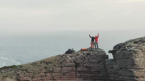 A picture of Jesse and Molly, with one arm around each other and the other arm in the air on top of the old man of hoy. Alastair is in shot, filming our celebration.