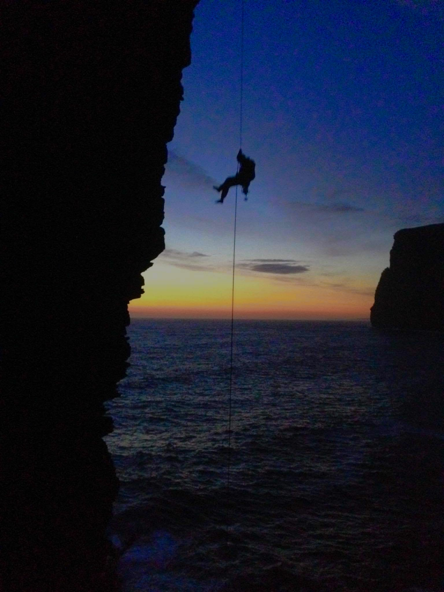 A picture of Jesse on the last free hanging abseil to get down to the base of the sea stack. The sun is setting and he and the stack are silhouetted in the foreground. It is very nearly dark.