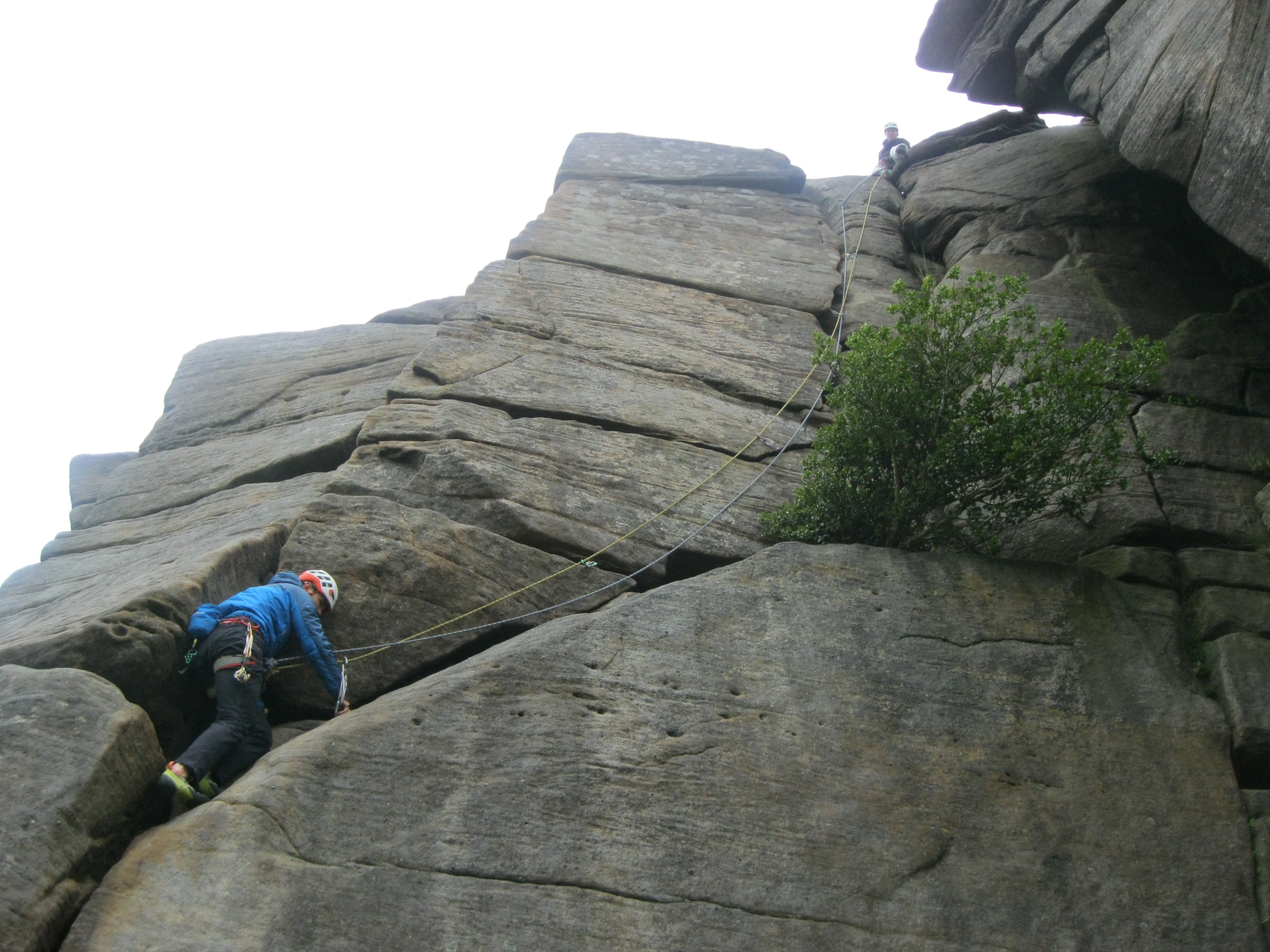 A picture of Molly sat at the top of the crag and Jesse climbing the route  on second.