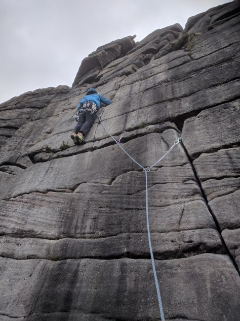 A picture of Jesse climbing Central Trinity at Stanage in his warm blue jacket