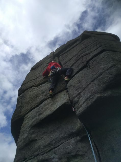 A picture of Jesse, in his windproof red jacket climbing The File at Higgar Tor
