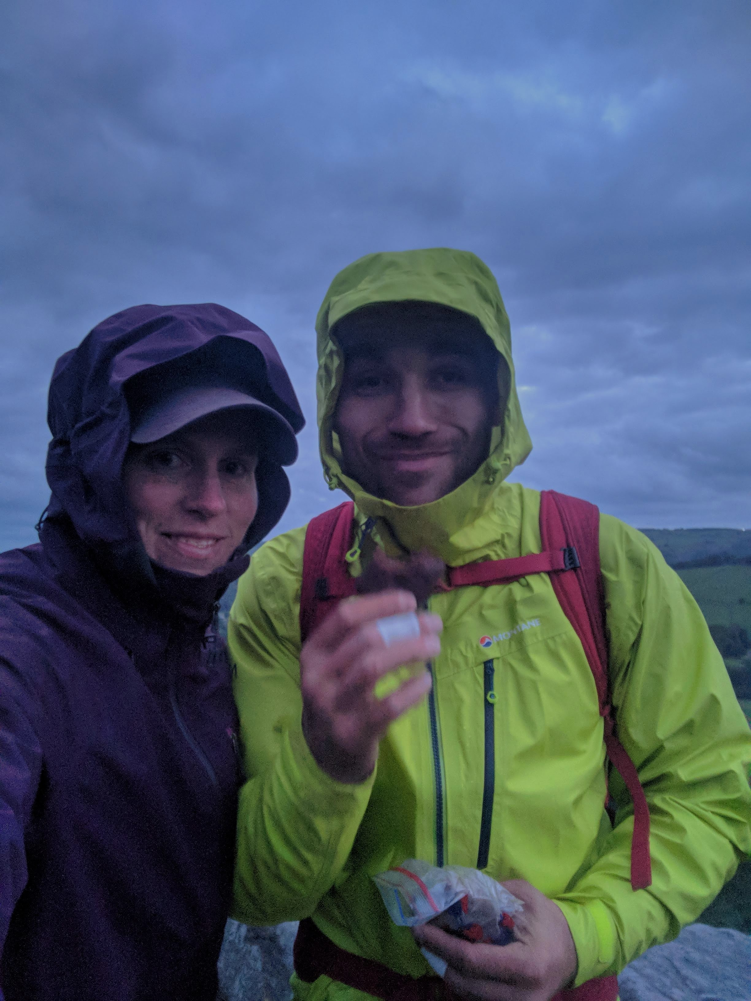 A picture of Molly and Jesse with their waterproof jackets on with hoods up, looking very tired, as it starts to get dark.