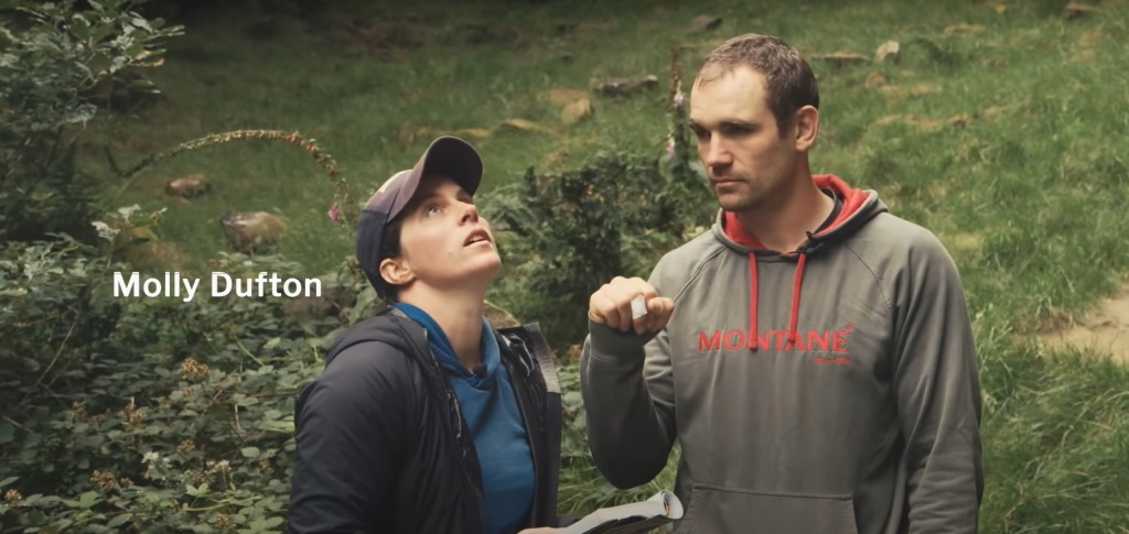 A picture of Molly and Jesse at the base of the crag with grass and shrubs in the background. Molly is holding the guidebook and is looking up at the route.  Jesse is looking towards Molly and listening intently to the verbal descriptions.