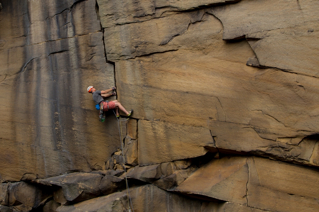 A picture of Jesse climbing Forked Lightning Crack in Yorkshire. Jesse is wearing shorts (not a good choice for a gritstone crack...). He is sideways on to the rock in a layback position. His two hands are pulling sideways in a vertical crack and his feet are on the right hand side of the crack, pushing his body to the left. It looks like a very strenuous position. The rope is below him and several pieces of gear have been placed in cracks and clipped to the rope.