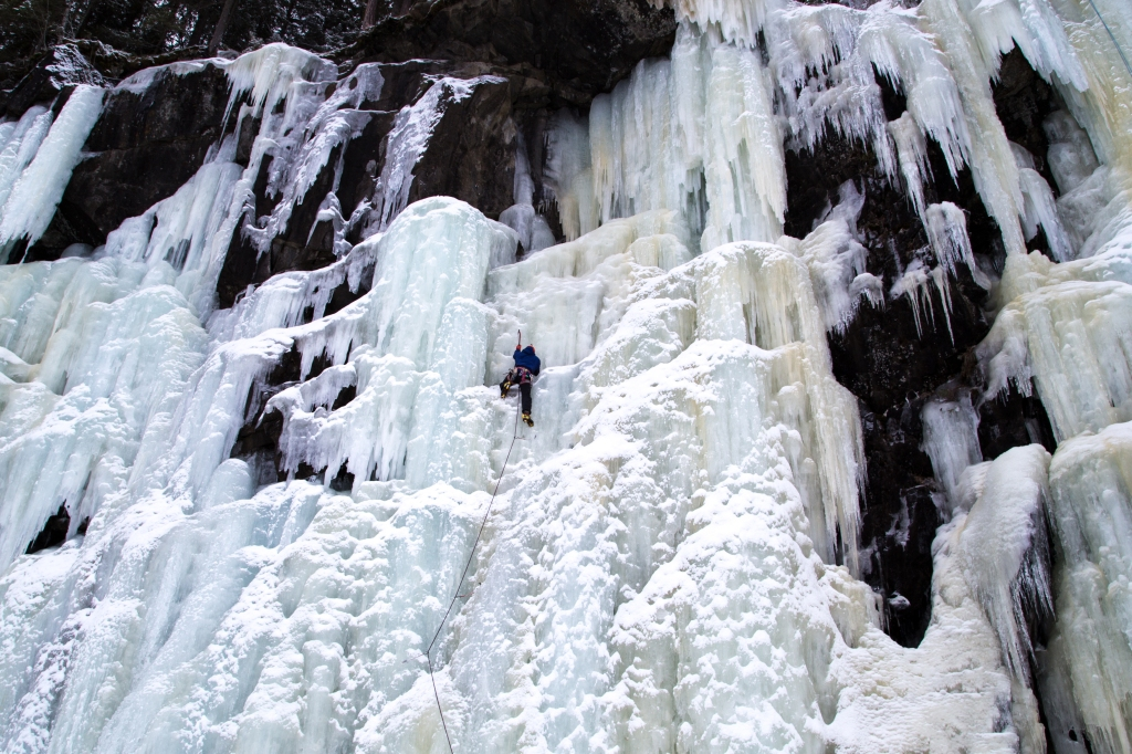 A picture of Jesse ice climbing on a huge frozen waterfall in Norway. He is leading up with the rope below him, and swinging his axe into the ice. The ice has formed in hanging chandeliers which looks quite spectacular.