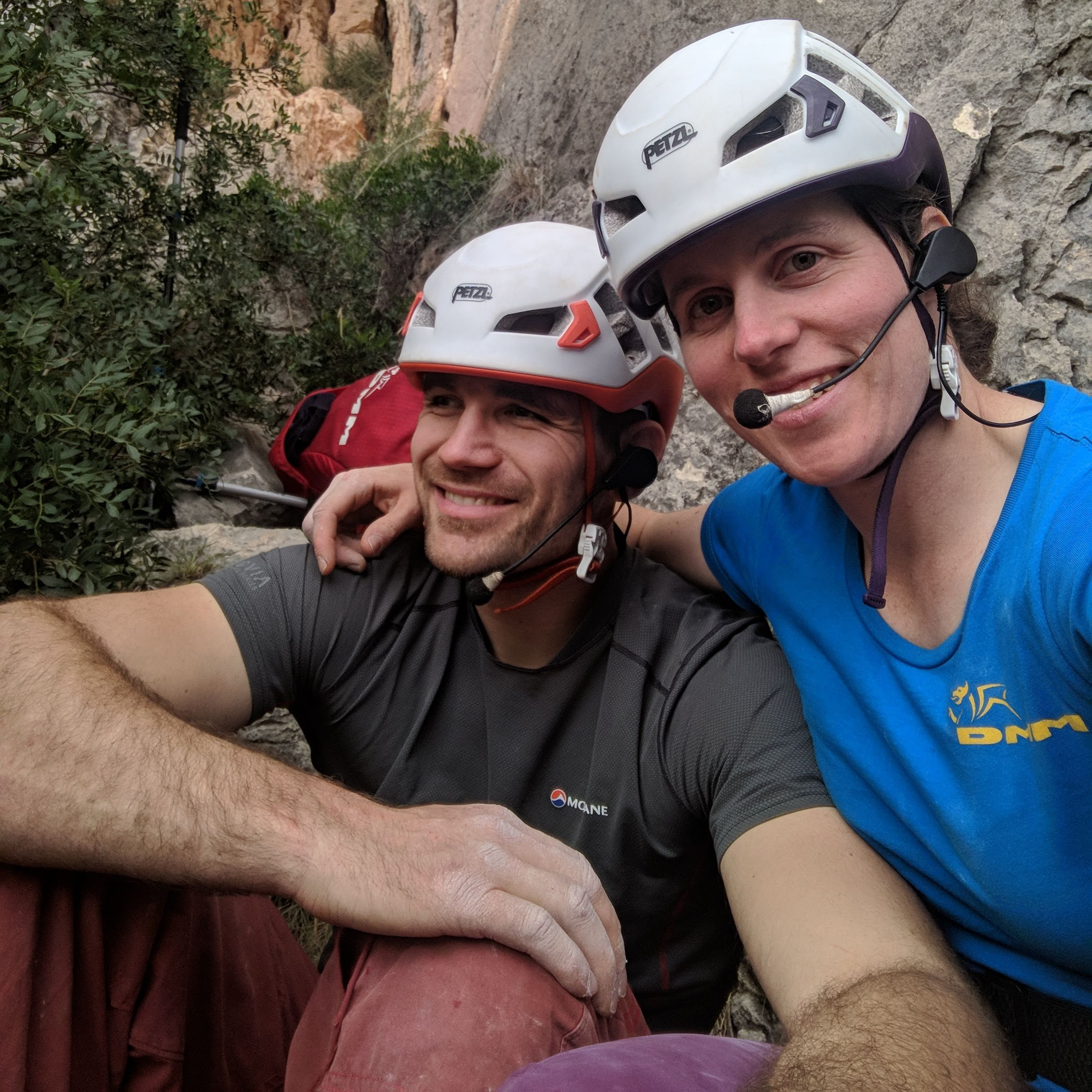 A photo of Jesse and Molly with the helmets and headsets on, sitting at the base of a crag. They both have big smiles on their faces.