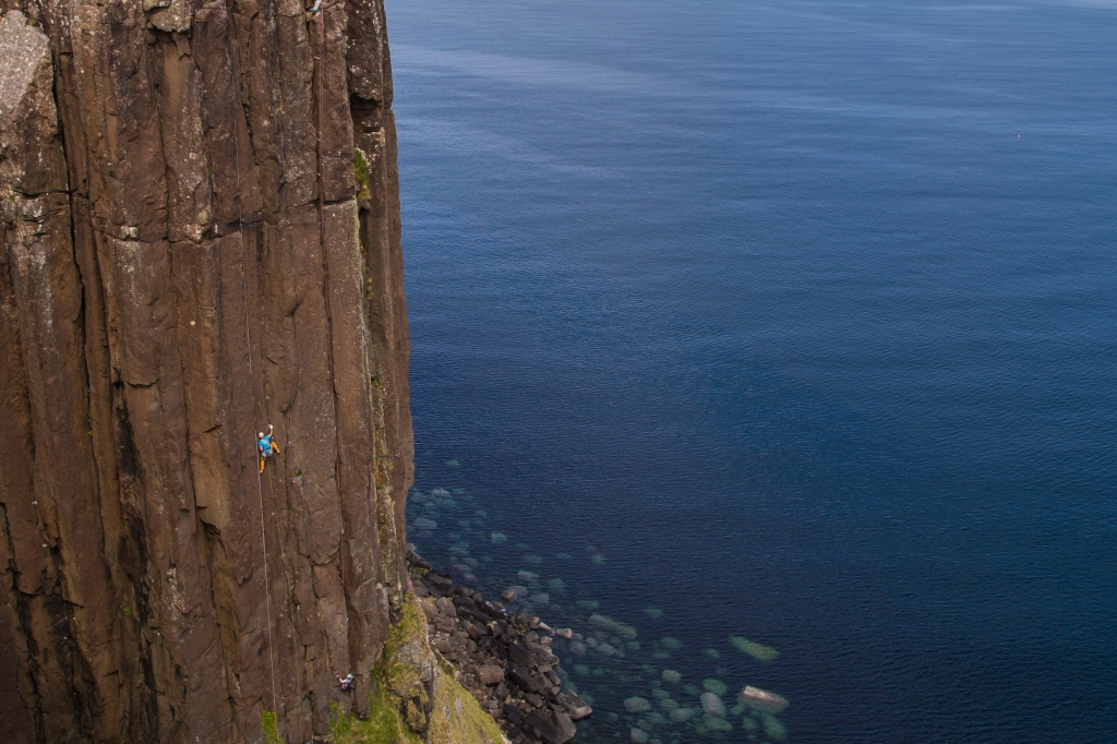 A photo of Jesse leading Grey Panther at Kilt Rock on the Isle of Skye.